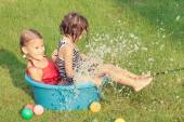 Brother and sister playing with water near a house — Stock Photo