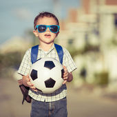 Caucasian little boy standing on the road and holding his soccer — Stock Photo