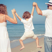Happy family walking on the beach at the day time. — Stock Photo