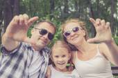 Happy family sitting on the bench in park — Stock Photo