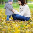 Young mother with her little baby in the autumn park — Stock Photo #54932265