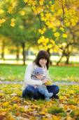 Young mother with her little baby in the autumn park — Stock Photo