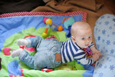 Little baby playing on bright carpet  — Foto Stock