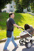 Man walking with baby stroller — Stock Photo