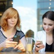 Two young girls using their smart phone — Stock Photo #62463617