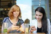 Two young girls using their smart phone  — Stock Photo