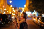 Woman with her little baby at the night city — Stockfoto