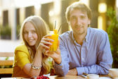 Couple holding glass of juice (focus on glass) — Stock Photo
