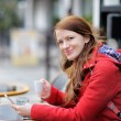 Young woman drinking coffee and using her smart phone — Stock Photo #67391105