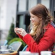 Young woman taking mobile photo of her cup of coffee — Stock Photo #67931851