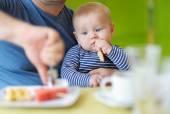 Baby boy having piece of bread  — Stock Photo