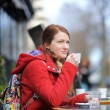 Woman drinking coffee in a street cafe — Stock Photo #68621939