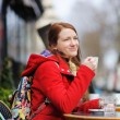Young woman drinking coffee in a street cafe — Stock Photo #73066885