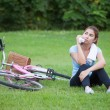 Happy Young Woman riding bicycle outside — Stock Photo #53435397