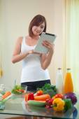 Young woman Following Recipe On Digital Tablet — Stock Photo