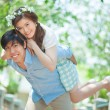 Young man giving a piggy back to his girlfriend — Stock Photo #65024939
