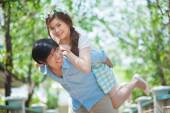 Young man giving a piggy back to his girlfriend — Stock Photo