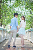 Loving asian couple under tree in the park — Stock Photo