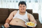 Lazy overweight male sitting with fast food — ストック写真