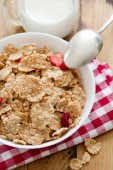 Cereals with dry fruits in white bowl and milk — Stock Photo