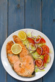 Fried salmon with vegetable salad and lemon on white plate — Stock Photo