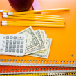 Notebooks, pencils, calculator, cash and apple School supplies — Stock Photo #52330587