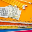 Notebooks, pencils, calculator, cash and apple School supplies — Stock Photo #52330603