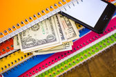 Phone, dollars and notebooks, School supplies — Stock Photo