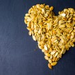 Pumpkin seeds in shape of heart — Stock Photo #56593357