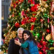 Mature couple getting photographed at Christmas tree — Stock Photo #58845671