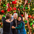 Mature couple getting photographed at Christmas tree — Stock Photo #58845869