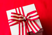 Box with red and white ribbon — Stock Photo