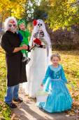 Family in costumes on Halloween night — Stock Photo