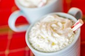 Hot chocolate with whipped cream and peppermint stirrer — Stock Photo