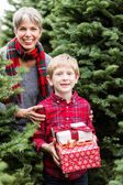 Family at Christmas tree farm with gifts — Stockfoto