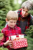 Family at Christmas tree farm with gifts — Stock Photo