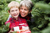 Family at Christmas tree farm with gifts — Photo