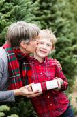 Family at Christmas tree farm with gift — Stock Photo