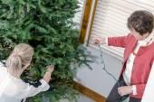 Family decorating Christmas tree — Stock Photo