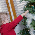 Little boy decorating Christmas tree — Stock Photo #60060061