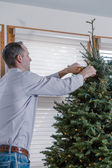 Young man decorating Christmas tree — Stock Photo