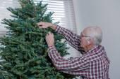 Grandfather decorating Christmas tree — Stock Photo