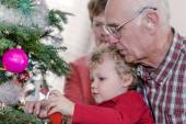 Grandparents with grandson decorating Christmas tree — Stock Photo