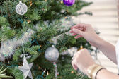 Beautiful woman decorating Christmas tree — Stock Photo