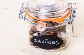 Saving money into glass jar — Stok fotoğraf