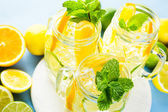Water with fresh citrus fruits and ice — Stock Photo