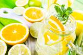 Water with fresh citrus fruits and ice — Stock fotografie