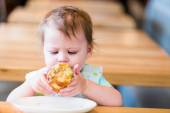 Little girl eating muffin — Stock Photo