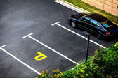 Look down empty parking spot with vegetation and shrubbery  from — Stock Photo