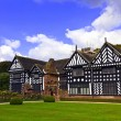 Black and white timber framed medieval mansion house and gardens. — Stock Photo #53771083
